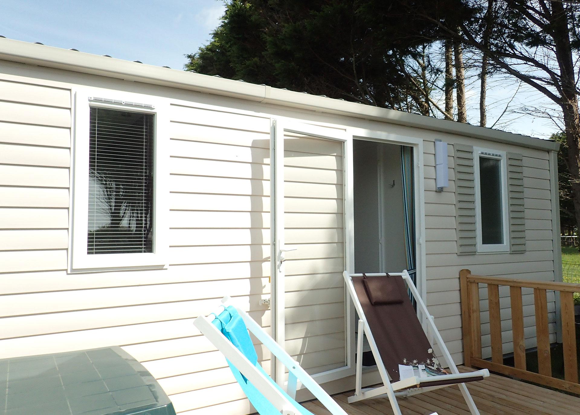 Terrasse extérieure en bois avec deux bains de soleil du mobil home famille