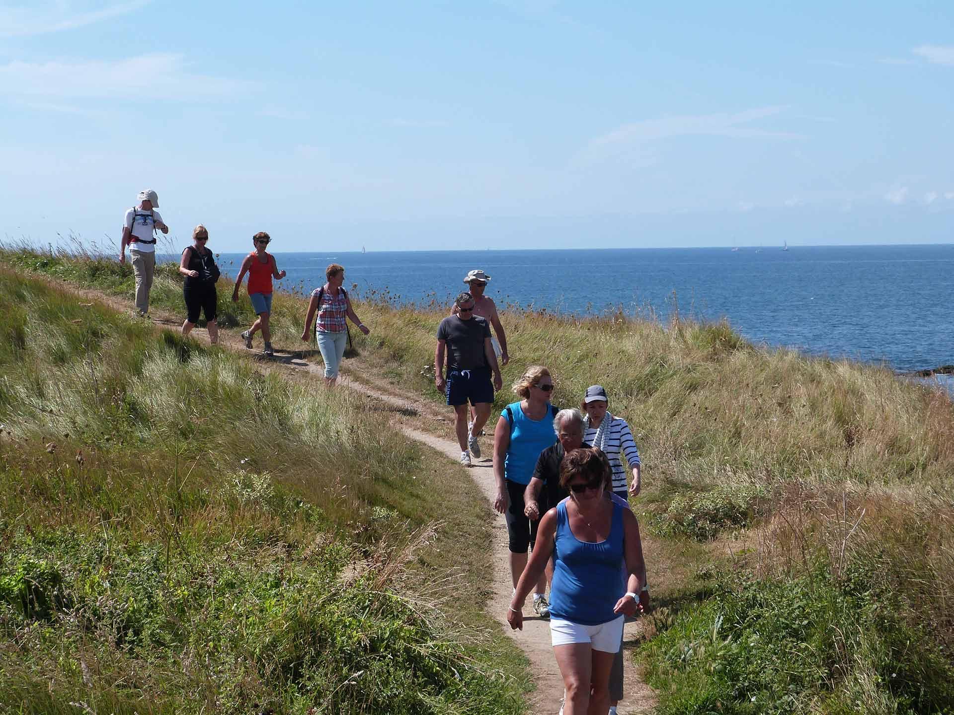 Des randonneurs marchent sur le sentier littoral près du camping Le Suroît