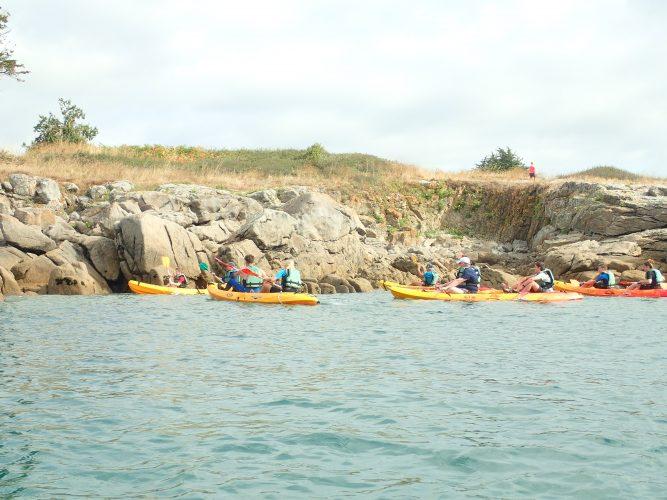 Des kayaks de mer mer longent la côte pour une rando en mer organisée par le camping le suroît